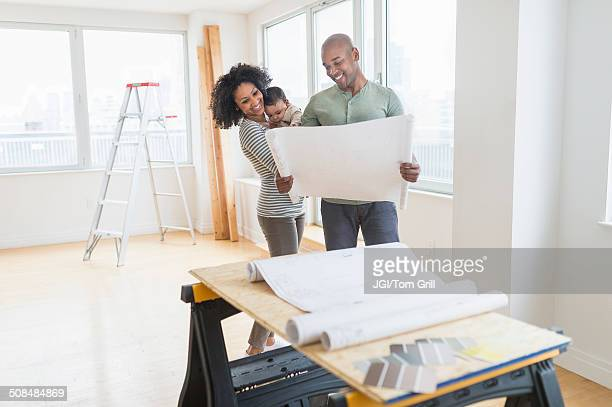 Family examining blueprints in new home