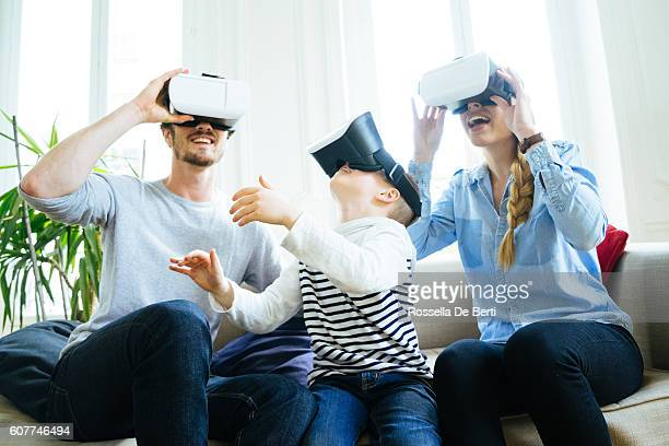 Family Experiencing Virtual Reality And Having Fan At Home