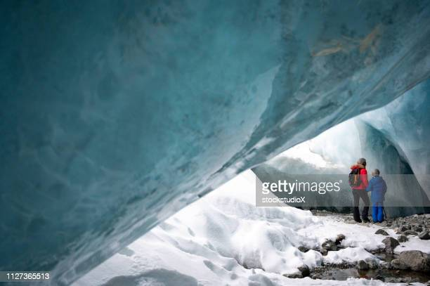 family exploring a stunning glacial ice cave - whistler british columbia stock pictures, royalty-free photos & images