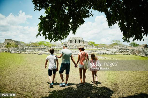 Family exploring Mayapan ruins during vacation