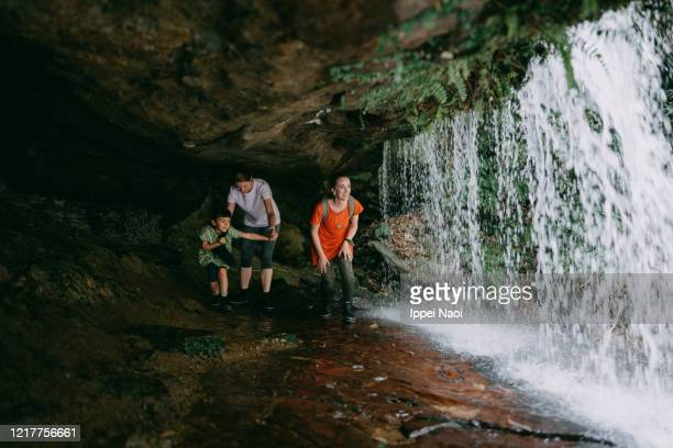 family exploring waterfall from behind - behind waterfall stock pictures, royalty-free photos & images