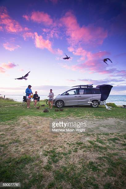 A family feeds the birds at sunset