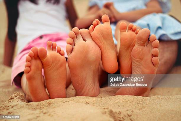 Family feet at the beach