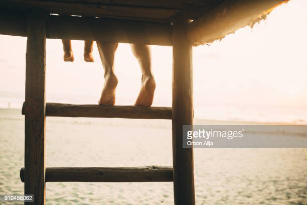 Family Feet hanging from a hut above beach