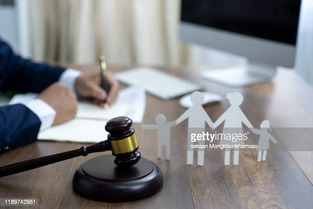 family figure and gavel on wooden table. family law concept - family politics stock pictures, royalty-free photos & images