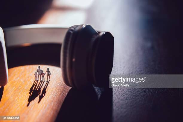 Family figurines standing between big earphones