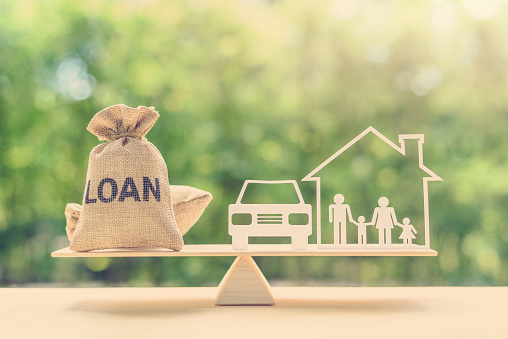 Family financial management, mortgage and payday loan or cash advance concept : Loan bags, family in a house on balance scale, depicts short term borrowing, high interest rate based on credit profile 1058480452
