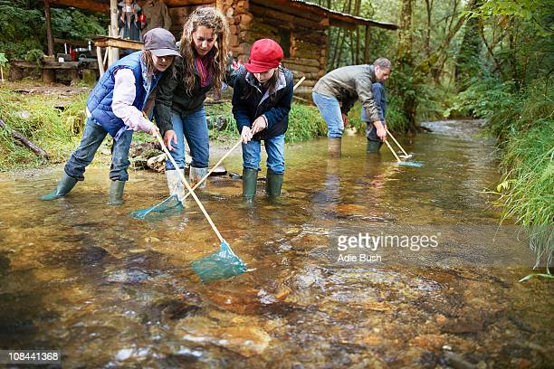Family fishing with nets in a river