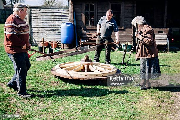 Family fit the metal tyre onto a wooden cartwheel, Wheelwrights