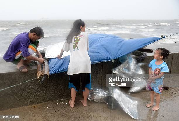 A family fix their temporary shelter during heavy wind and rains brought on by typhoon Koppu along Roxas boulevard in Manila on October 18 as the...
