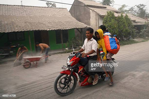 A family fleeing on a motorcycle during mass evacuation pass the ash covered village of Kediri in East Java province on February 14 2014 following...