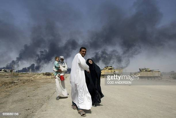 Family flees past British tanks as smoke billows from the southern Iraqi city of Basra 29 March 2003. Days of fighting has caused the population in...
