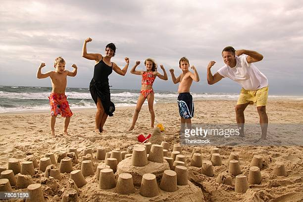 Family flexing on beach with sand castle