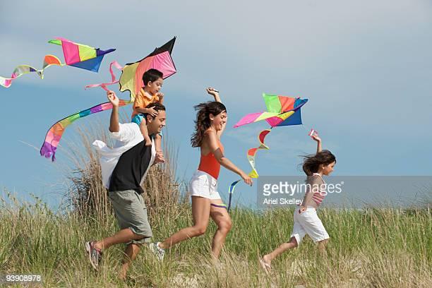 Family flying kites in field
