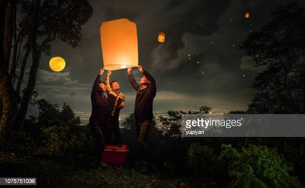 family flying lantern in loy krathong festival - candle of hope stock pictures, royalty-free photos & images