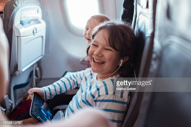 family flying on an airplane - aeroplane stock pictures, royalty-free photos & images