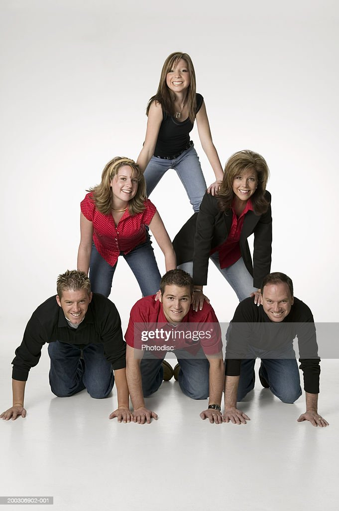 Family Forming Human Pyramid In Studio Portrait Stock Photo