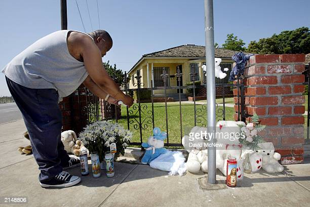 Family friend Charles Edward Booker Jr ties baby shoes at a makeshift memorial in front of the house where the day before a family of five was found...