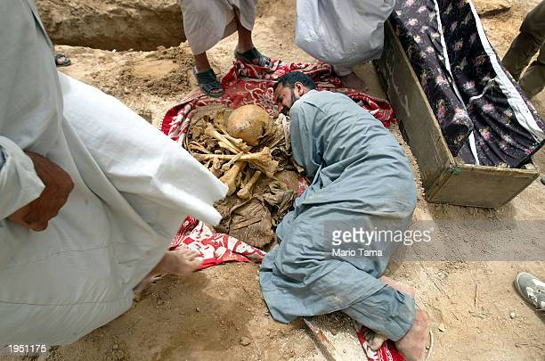 A family friend reacts after the body of political prisoner Waleed Mejeed was recovered at the alQarah cemetery April 25 2003 in Abu Ghraib Iraq...