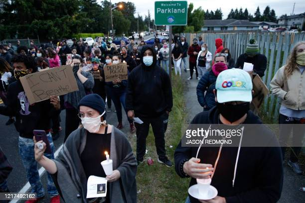 Family friends and community members attend a vigil at the intersection where Manuel Ellis a 33yearold black man died in Tacoma Police custody on...