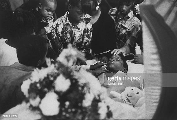 Family friends around open casket touching Robert Yummy Sandifer's face mourning at funeral for 11yrold Black Disciples member who killed 14yrold...