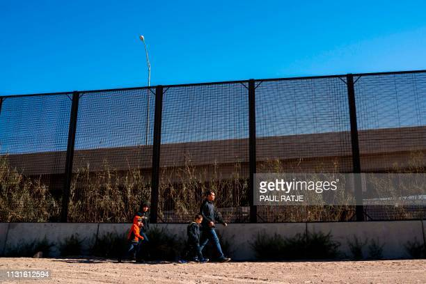 A family from El Salvador is pictured walking to turn themselves into Border Patrol agents after crossing the Rio Grande to claim asylum in El Paso...