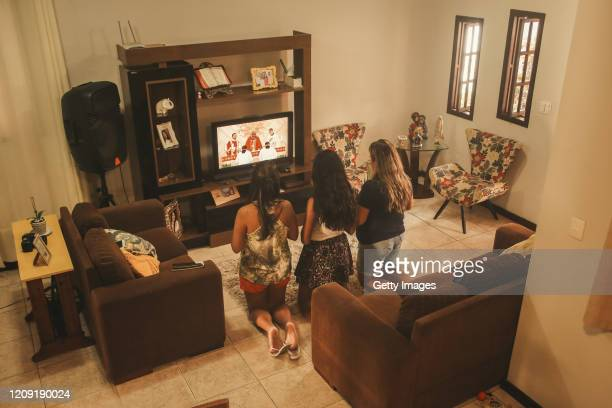 A family from Sao Goncalo follows the Palm Sunday Mass celebration on TV during the coronavirus pandemic on April 5 2020 in Niteroi Brazil According...