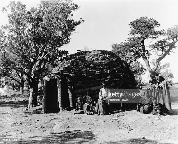 A family from the Hopi American Indian tribe poses outside of their hogan Arizona 1920s The man sits with a traditional conga drum