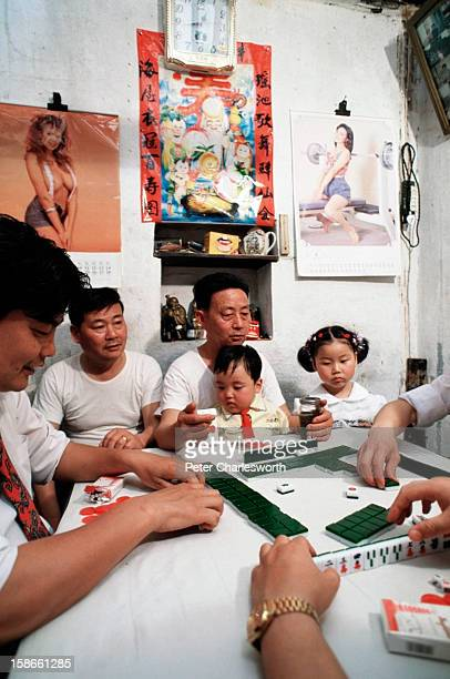A family game of Mahjong is played in a small house in Suzhou by parents and their children None of the children have brothers or sisters as the one...