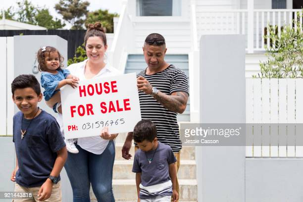 Family gather around For Sale sign in front of their house