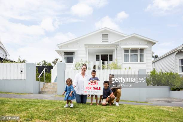 Family  gather around For Sale sign outside their home
