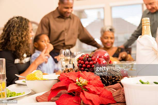 Family gather around the dinner table at Christmas time.