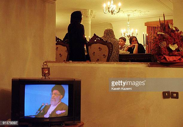 A family gather around the dinner table in the evening while the TV set is on in the foreground with an image of Ayatollah Ali Khamenei on the screen...