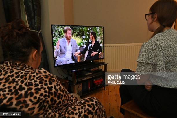 Family gather around the television in Liverpool, north west England to watch Prince Harry and his wife Meghan's explosive tell-all interview on CBS...