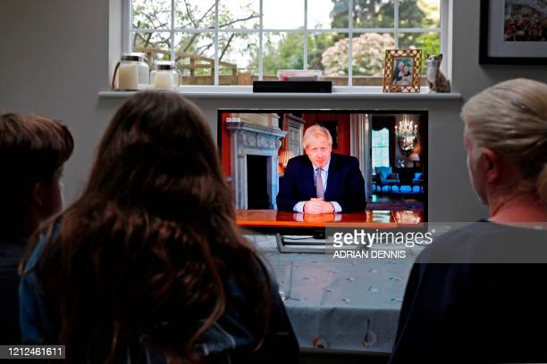 A family gather around the television to watch Britain's Prime Minister Boris Johnson give a televised message to the nation in Hartley Wintney west...