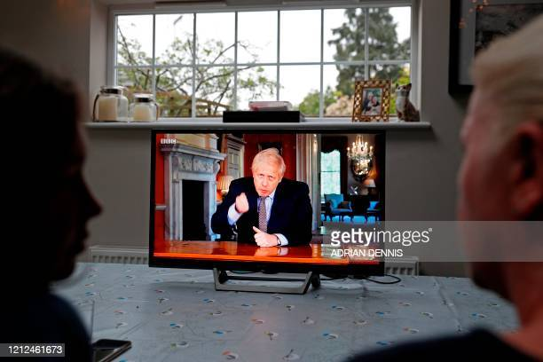 Family gather around the television to watch Britain's Prime Minister Boris Johnson give a televised message to the nation in Hartley Wintney, west...