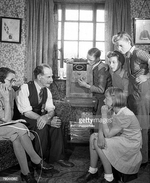 Family gather around the wireless to listen to the Victory in Europe Day radio broadcast to mark the end of European conflict in World War II,...