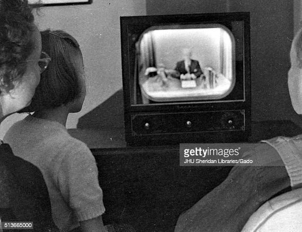 Family gathered around television set to watch American television host Lynn Poole on the Johns Hopkins Science Review 1951