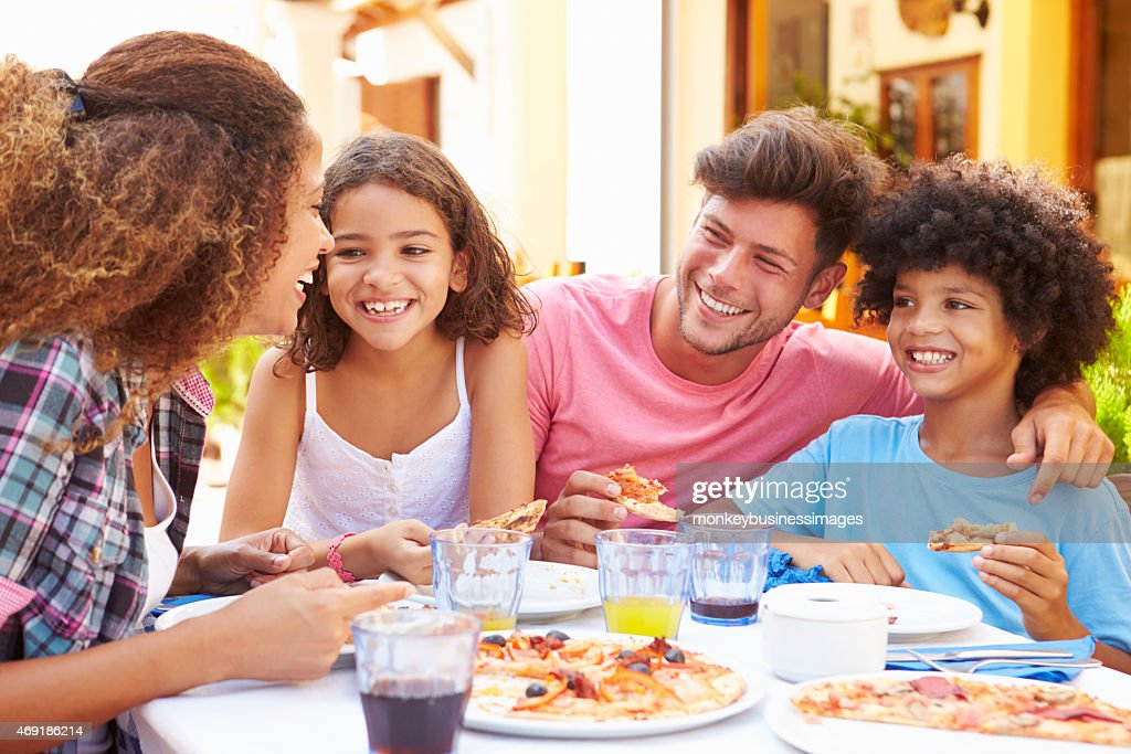 Family gathered at an outdoor restaurant to share a meal : Stock Photo