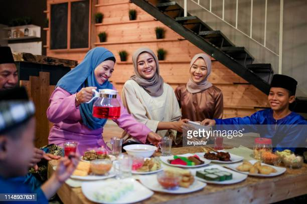 family gathering and eat together - hari raya celebration stock pictures, royalty-free photos & images
