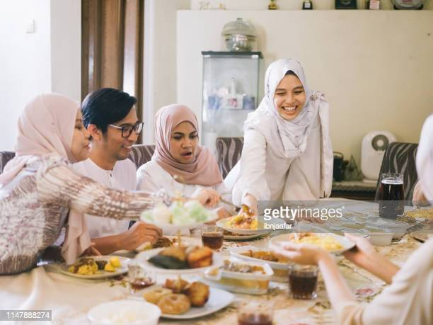 familientreffen und essen zusammen - eid al adha stock-fotos und bilder
