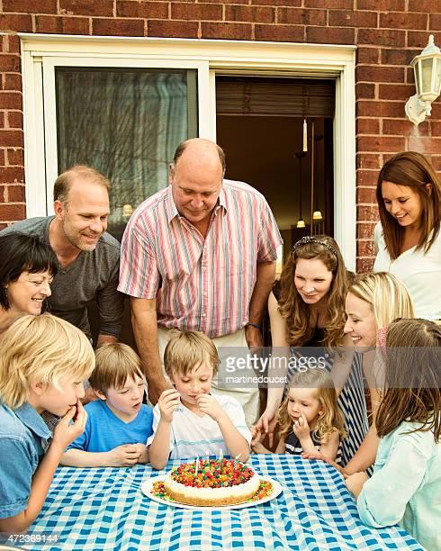 Reunión familiar en little boy para su cumpleaños con una porción de torta.