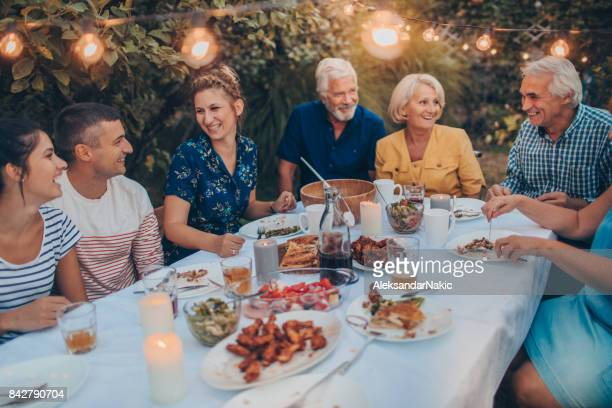 family gathering over dinner - outdoor party stock pictures, royalty-free photos & images