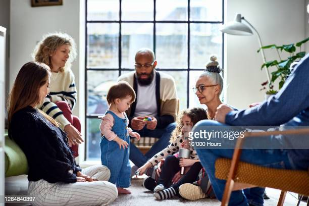 family gathering with two young children - multi ethnic group stock pictures, royalty-free photos & images