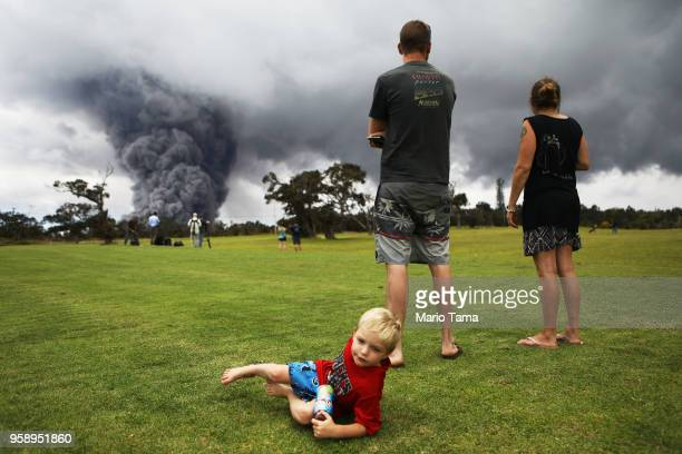 A family gathers at a golf course as an ash plume rises in the distance from the Kilauea volcano on Hawaii's Big Island on May 15 2018 in Hawaii...