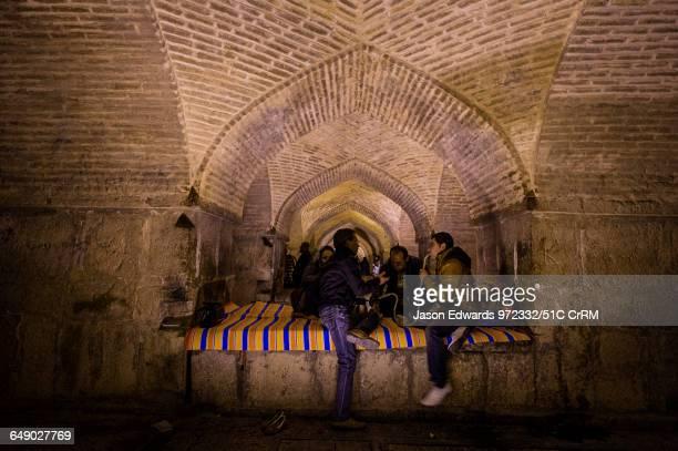 Family gathers beneath the vaulted ceiling of the khaju Bridge to smoke the hookah.