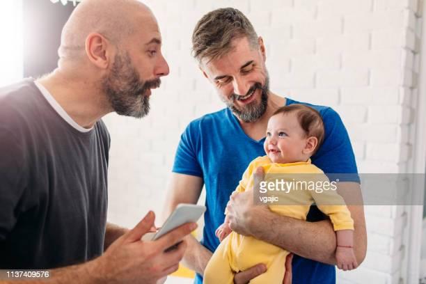 famille lgbtq-papas gays à la maison - couple de jeunes lesbiennes photos et images de collection