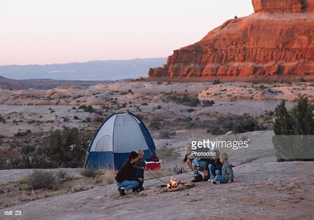family gets ready for dinner at their campfire in the desert