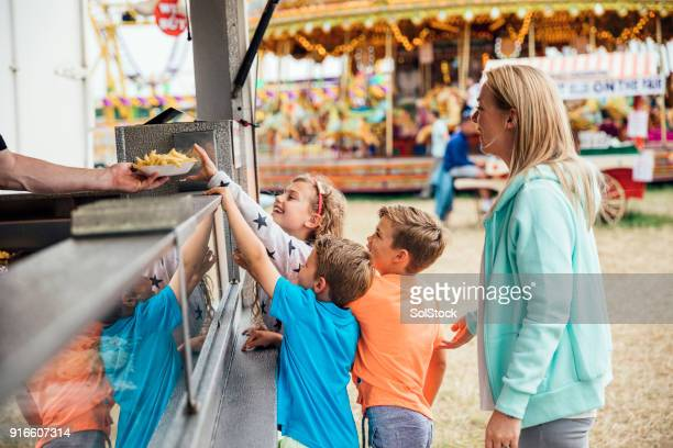 family getting food at the fairground - gala stock pictures, royalty-free photos & images
