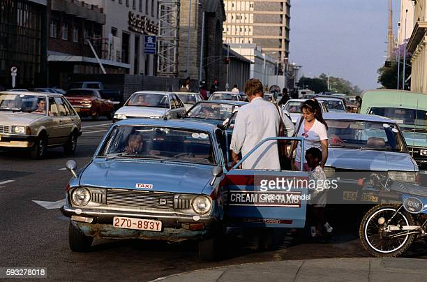 Family Getting into Taxi in Downtown Harare